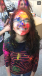 Young girl poses after an Indian Holi festival completely covered in colorful paint splatters